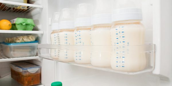 Бутылочки с молоком на дверце холодильника