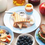 Завтрак — тосты, мюсли, фрукты, бутерброд, чай и сок