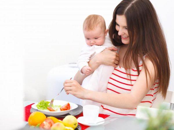 Мама держит ребёнка и ест салат
