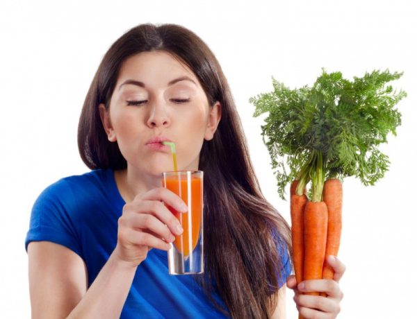 Свежая морковь и морковный сок в руках женщины