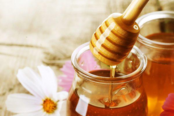 Мёд стекает с палочки в банку