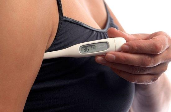Женщина измеряет температуру тела
