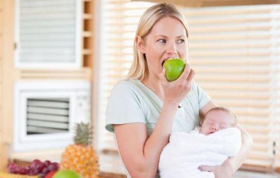 Женщина с ребёнком на руках ест яблоко