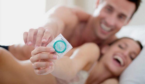 Мужчина и женщина держат презерватив