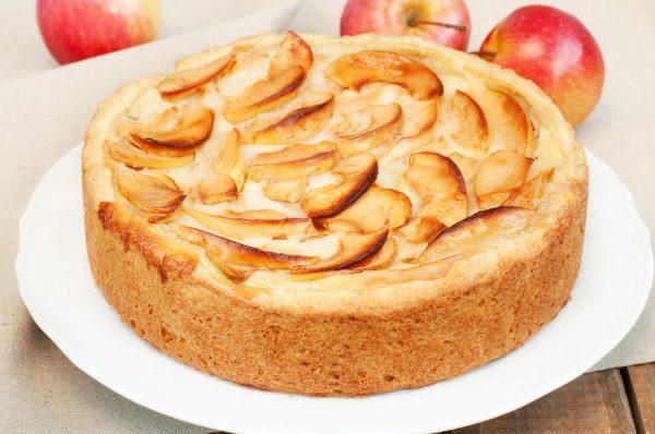 Яблочная шарлотка на тарелке и яблоки