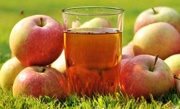 Яблочный сок в стакане и яблоки