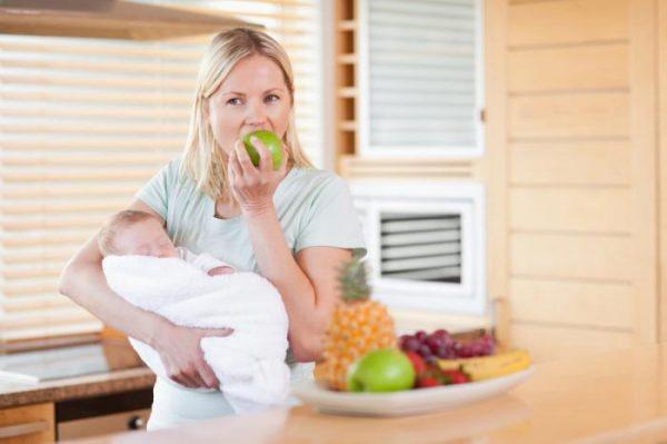 Женщина с грудничком на руках ест яблоко