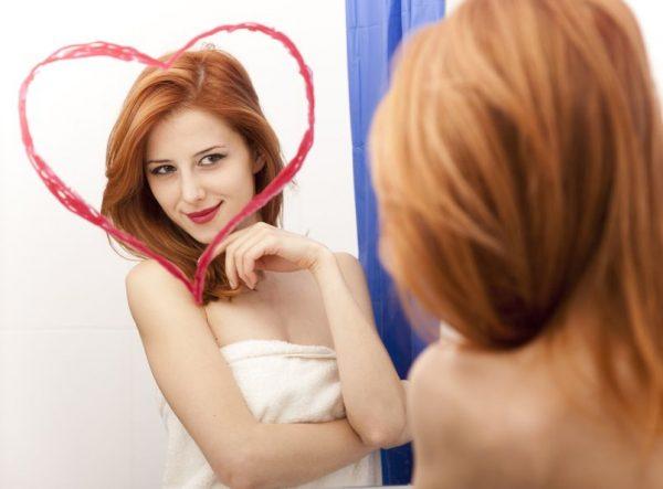 Женщина любуется на себя в зеркале