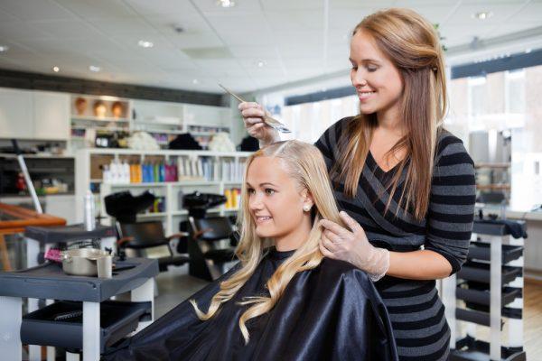 Женщине красят волосы в салоне