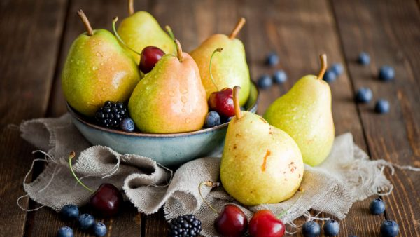 Груши и ягоды в тарелке и на столе