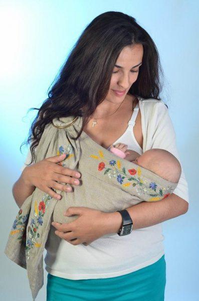 Мама кормит ребёнка в слинге