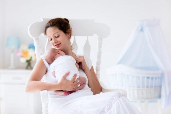 Молодая мама держит младенца на руках