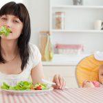 Молодая мама ест овощи