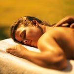 Мужчина делает женщине массаж в постели
