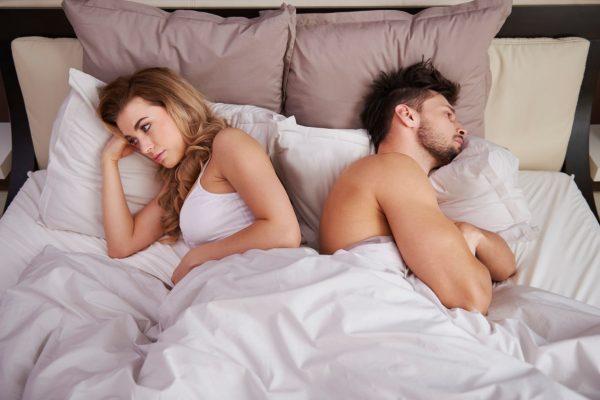 Супруги лежат в постели, отвернувшись друг от друга