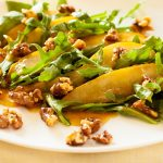 Тёплый салат с грушами и рукколой на тарелке