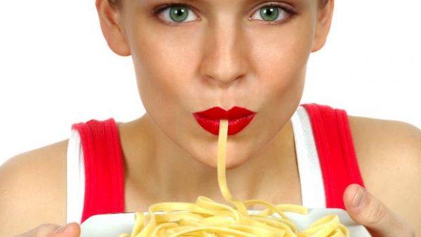 Женщина ест макароны
