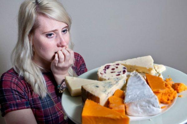 Женщина и тарелка с разными сортами сыра