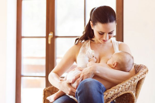 Женщина кормит ребёнка грудью