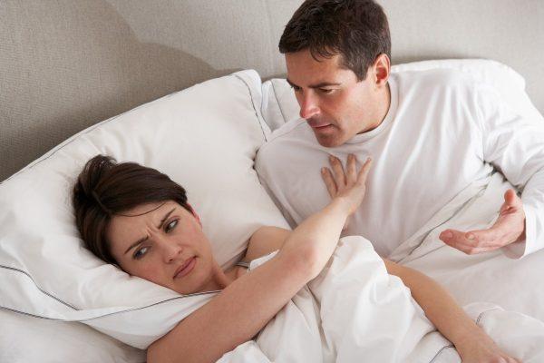 Женщина отталкивает мужчину в постели