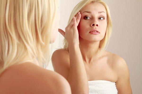 Женщина рассматривает себя в зеркало