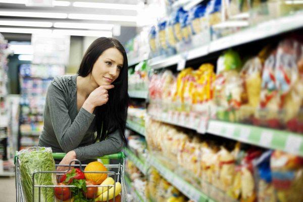 Женщина выбирает макароны в супермаркете