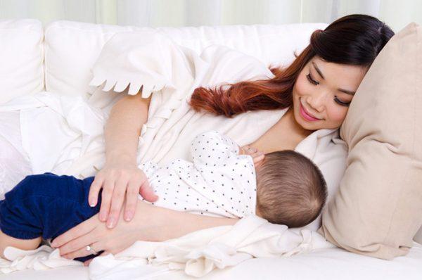 Женщина улыбается и кормит малыша лёжа на диване