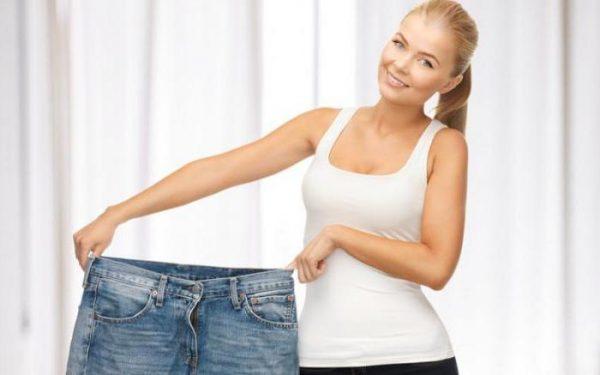 Женщина держит широкие джинсы