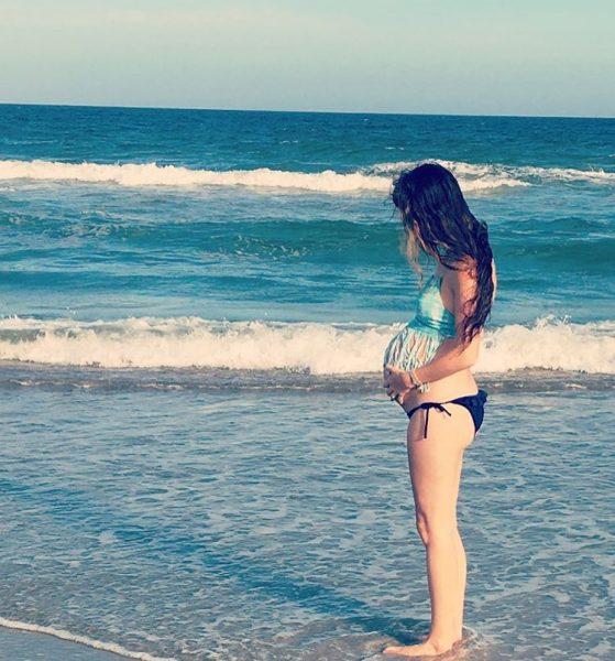 Беременная женщина в купальнике и топе на фоне моря