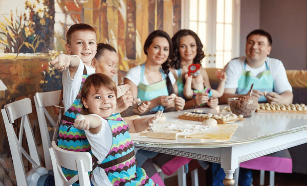 Члены семьи сидят за столом и лепят пельмени