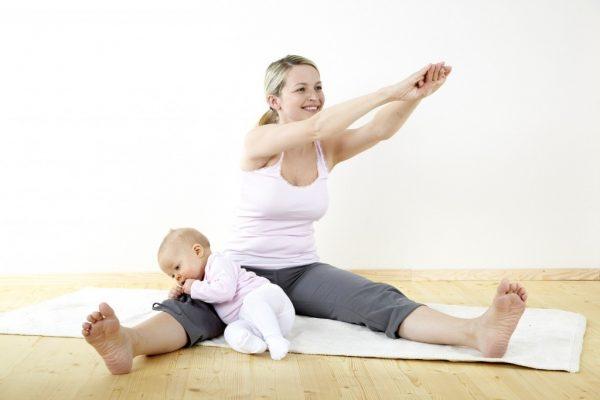 Девушка занимается спортом с малышом на руках