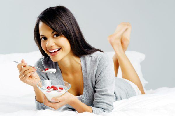 Женщина лежит на животе, держит в руках тарелку и ложку с творогом