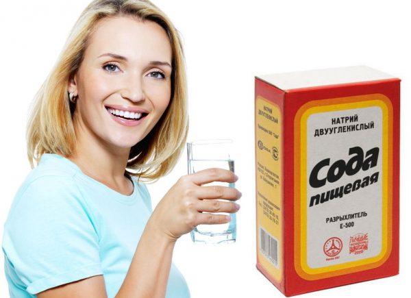 Улыбающаяся женщина со стаканом в руке и упаковка соды