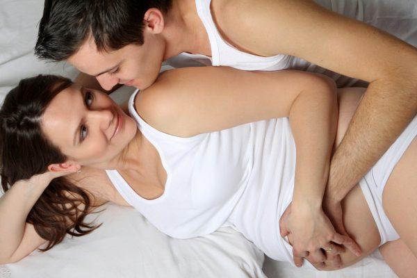Муж и беременная жена лежат на боку