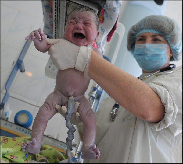 Акушерка показывает новорождённого с пуповиной