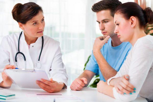 Беременная женщина с мужем консультируются с врачом