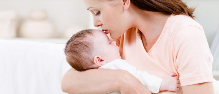 Женщина держит младенца на руках, целуя его в лоб