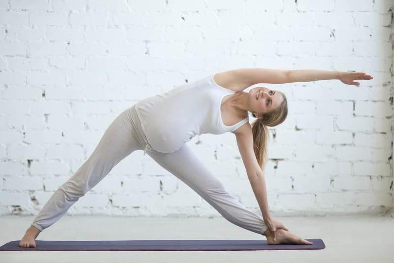 Беременная выполняет упражнение из йоги