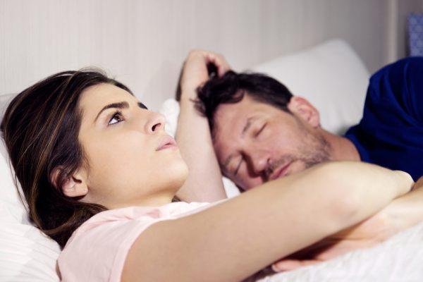 пара в постели — женщина смотрит в потолок, мужчина спит