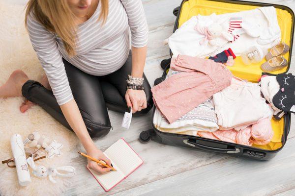 Женщина в положении делает записи в блокнот и собирает вещи