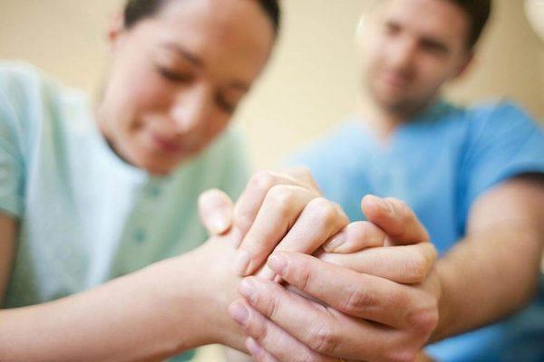 Мужчина держит женщину за руки