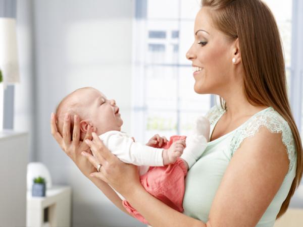 мама держит младенца на весу