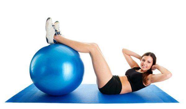 девушка делает упражнение с фитболом