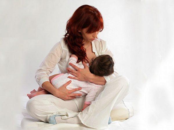 женщина кормит грудью ребёнка, сидя скрестив ноги