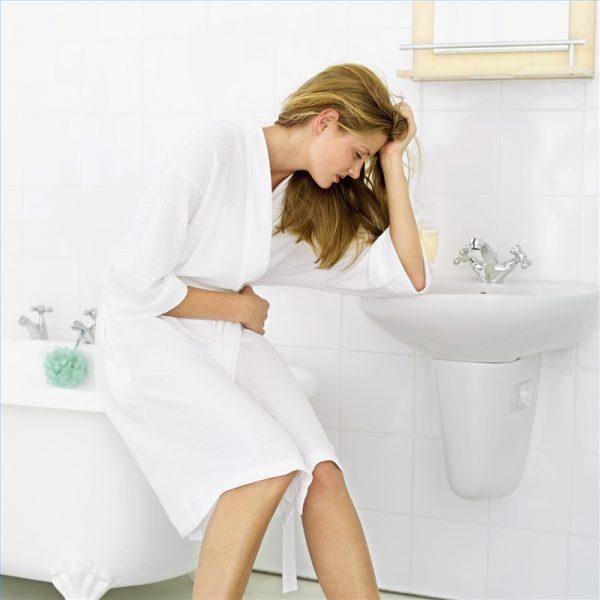 женщина в ванной сидит, склонившись над раковиной и закрыв глаза