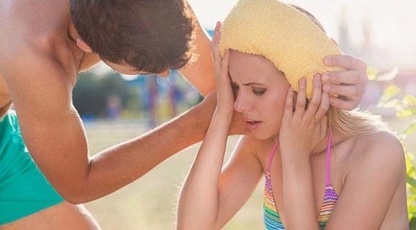 Мужчина прикладывает женщине к голове полотенце