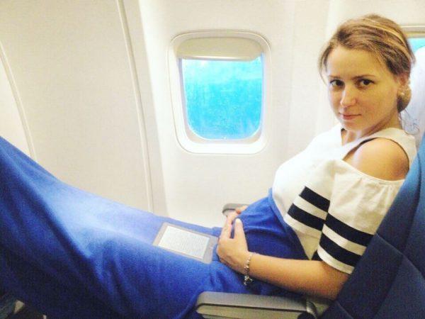 беременная сидит в самолёте у иллюминатора