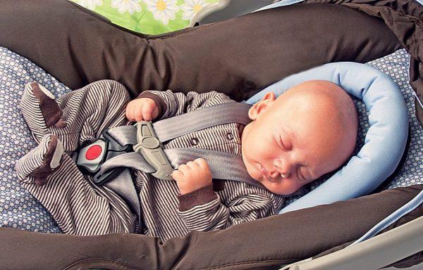 новорождённый в автокресле, пристёгнутый ремнями