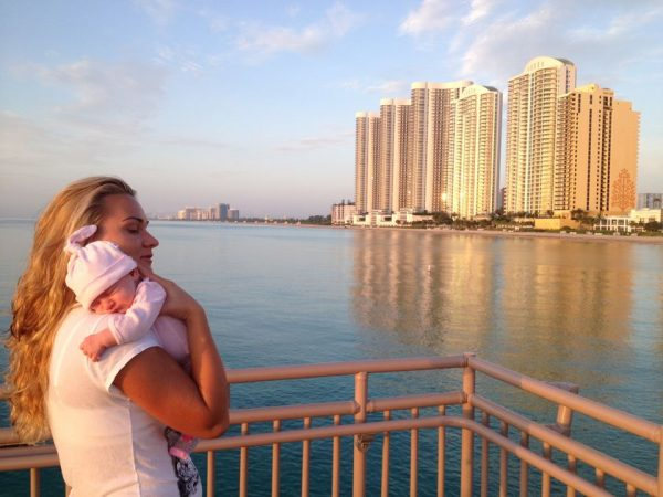 женщина с младенцем на балконе с видом на море