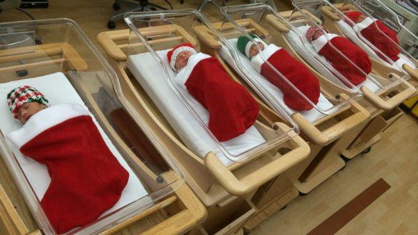 новорождённые в рождественских носках для подарков